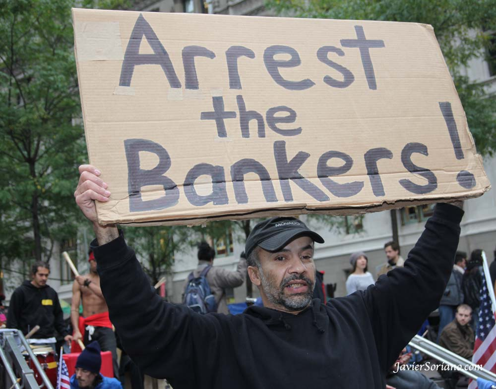 "October 2011 - A protester in support of Occupy Wall Street at Liberty Plaza holding a sign, ""Arrest the bankers"". On Saturday, September 17th, 2011 the Occupy Wall Street Movement started in Zuccotti Park. Photo by Javier Soriano/www.JavierSoriano.com"