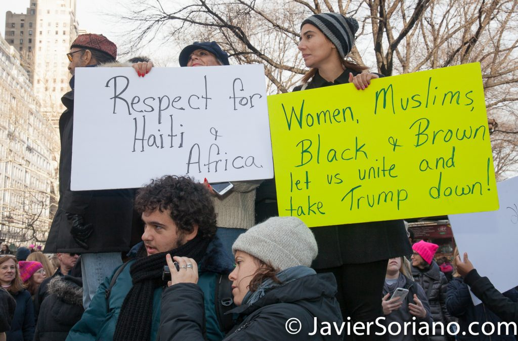 "1/20/2018. Manhattan, NYC - Women's March. People watching the march. ""Respect for Haiti and Africa."" ""Women, Muslims, Black and Brown let us unite and take Trump down.""  Photo by Javier Soriano/www.JavierSoriano.com"
