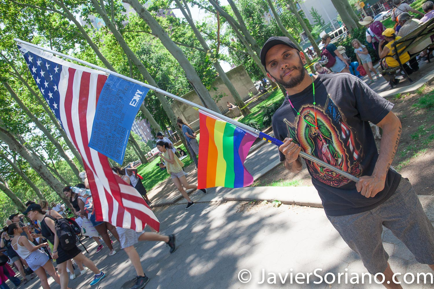 "6/30/2018. March: ""Families Belong Together."" People at Cadman Plaza. People's protectors marched from Foley Square in Manhattan to Cadman Plaza in Brooklyn. Man with the Gay flag, the United States American flag and a t-shirt with the Virgin of Guadalupe. Photo by Javier Soriano/www.JavierSoriano.com"