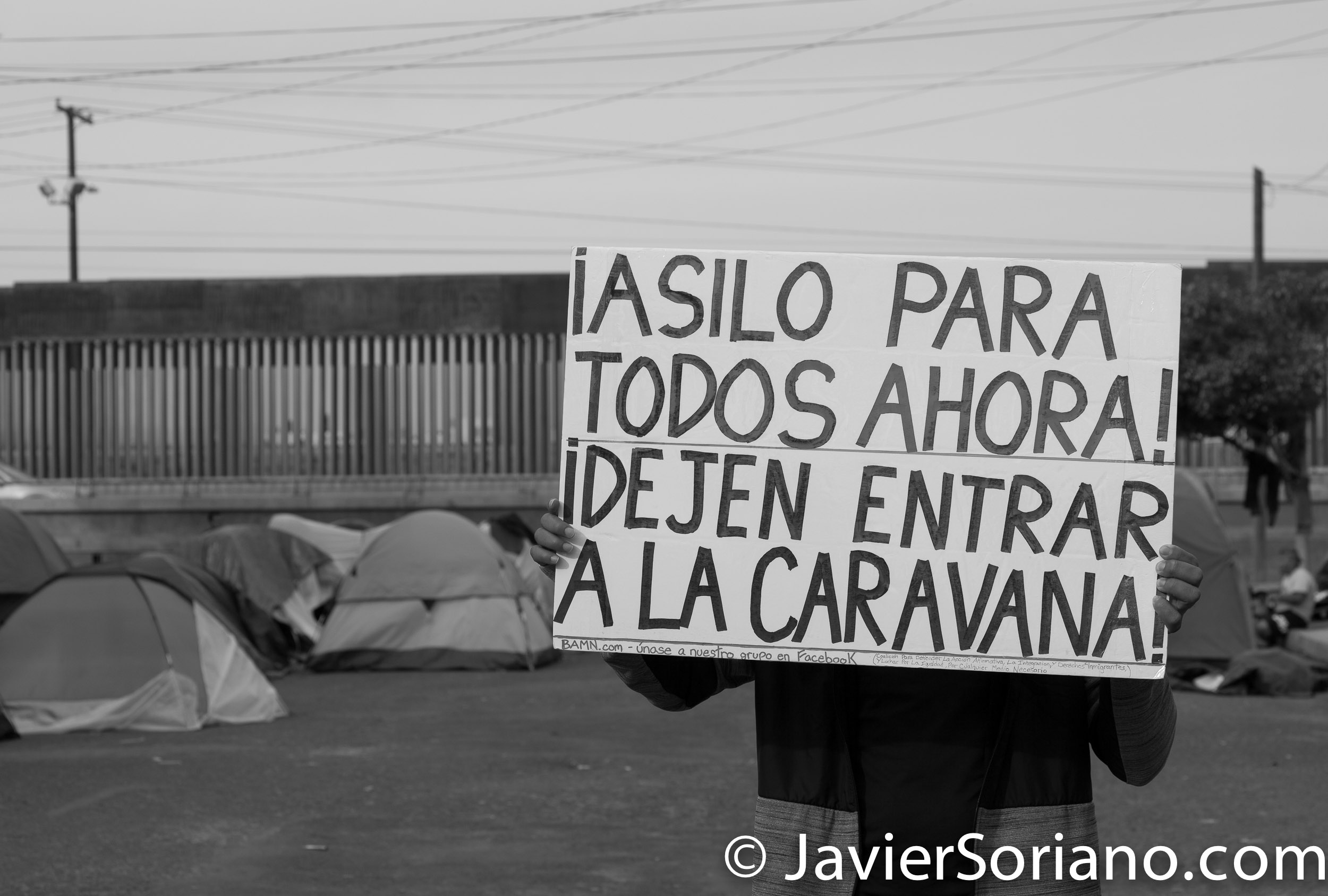"THIS PHOTO: Refugee from Centro America in Tijuana, Mexico. December/2018. Behind him is the Mexico - US border. The sign reads: ""Asylum for everyone now! Let the caravan enter (the United States of America)"". ESTA FOTO: Refugiado de Centro America en Tijuana, México. Diciembre/2018. Detrás de él está la frontera entre México y Estados Unidos. El cartel dice: ""¡Asilo para todos ahora! Dejen entrar a la caravana (a los Estados Unidos de América)"". Photo by Javier Soriano/JavierSoriano.com"