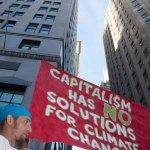 "9/22/2014. NYC - ""Capitalism has no solutions for climate change."" A protester on Broadway and Wall St. in the lower Manhattan (""El capitalismo no tiene soluciones para el cambio climático."" Un manifestante en Broadway y Wall St. en el bajo Manhattan)."