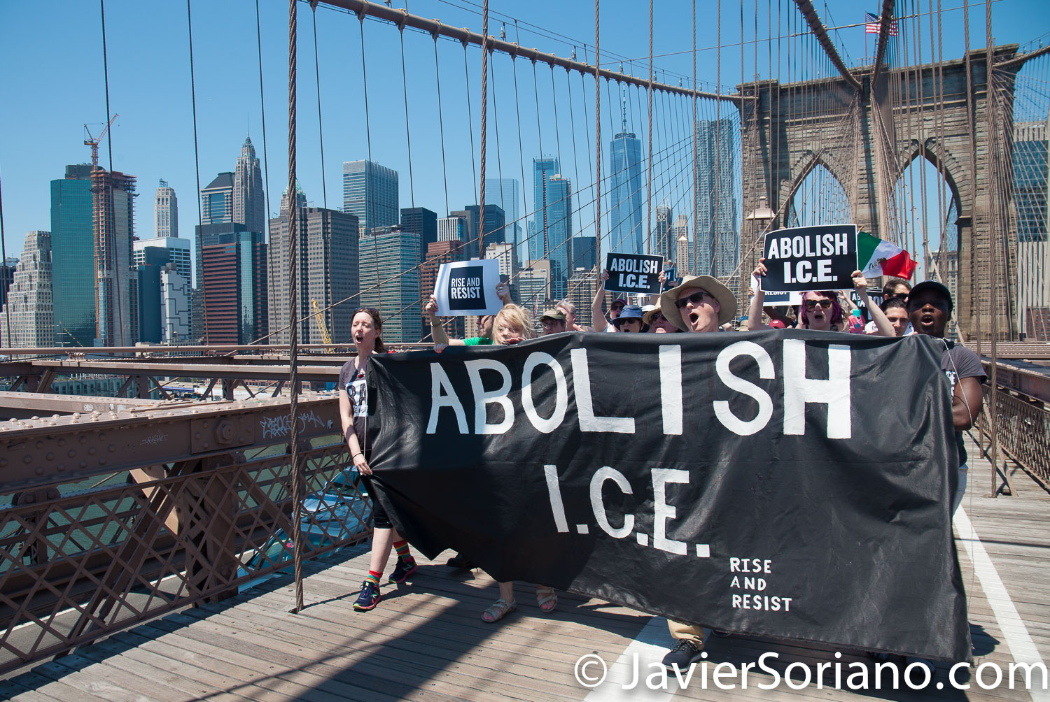 """6/30/2018. March: """"Families Belong Together."""" People crossing the Brooklyn Bridge. People's protectors are marching from Foley Square in Manhattan to Cadman Plaza in Brooklyn. The banner says: """"ABOLISH I.C.E.""""_Rise and resist Photo by Javier Soriano/www.JavierSoriano.com"""