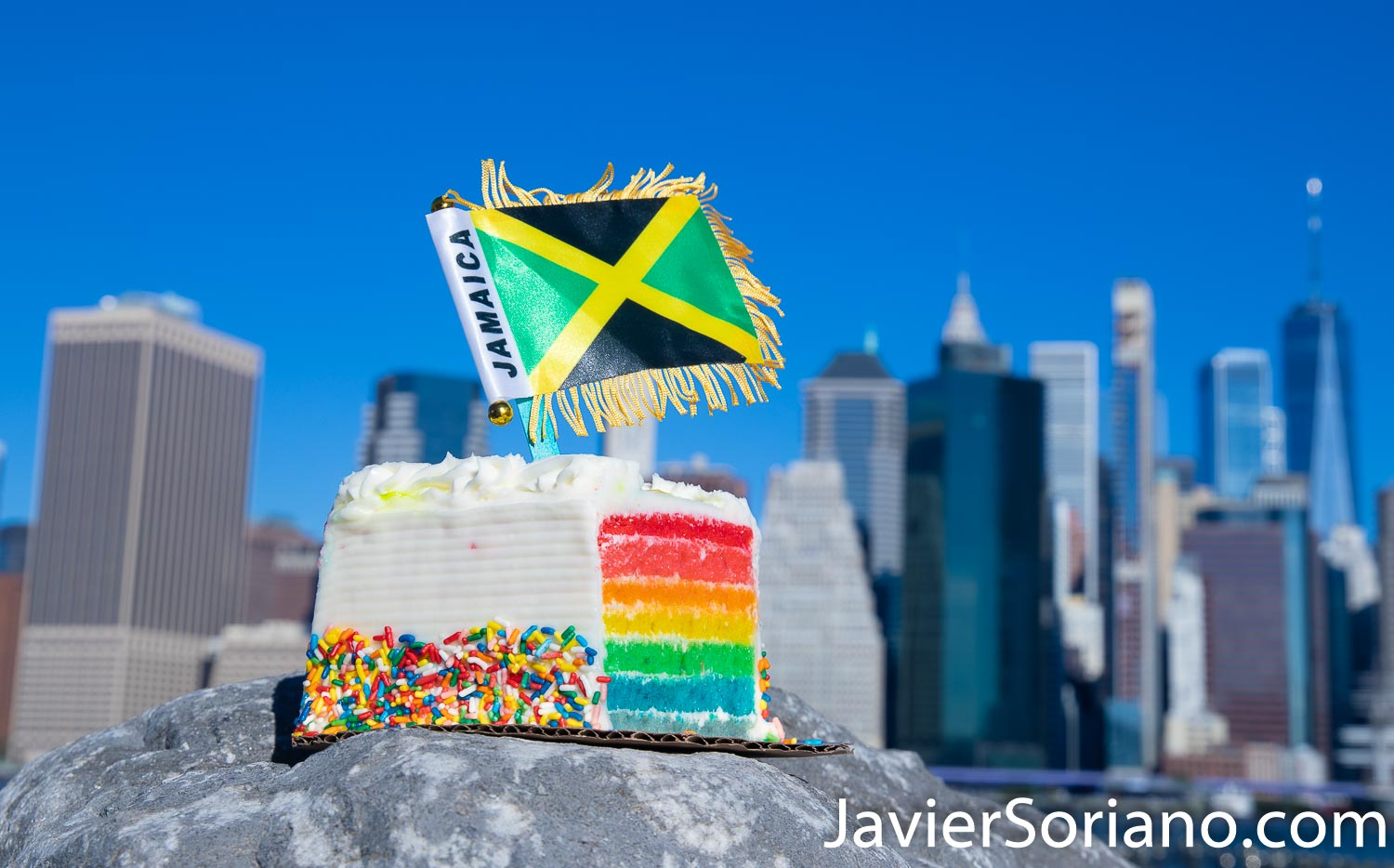 Rainbow cake and the flag of Jamaica. The background is the Lower Manhattan, also known as Downtown Manhattan or Downtown New York City. Photo by Javier Soriano/www.JavierSoriano.com