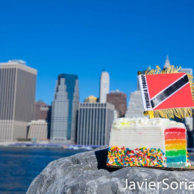 Rainbow cake and the flag of Trinidad and Tobago. The background is the Lower Manhattan, also known as Downtown Manhattan or Downtown New York City. Photo by Javier Soriano/www.JavierSoriano.com