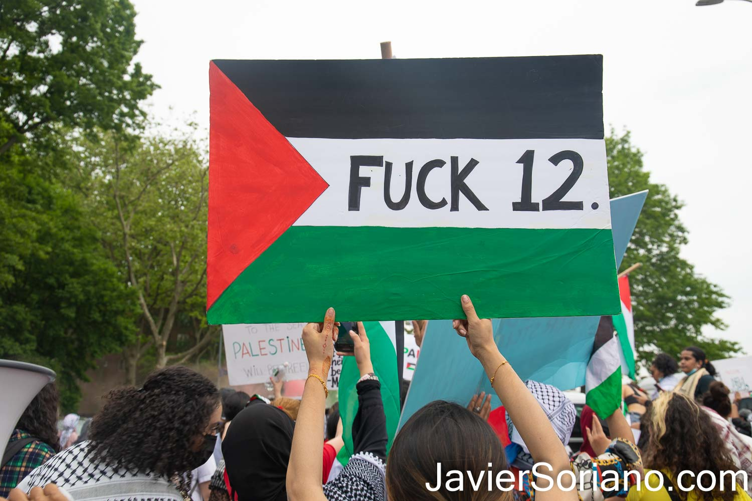 """Saturday, May 22, 2021. New York City -  Thousands of anti-zionist Palestinians, Jews, Native Americans, Latinas, Latinos, Blacks, Asians, and others rallied and marched to DEFEND PALESTINE.   Demonstrators gathered at Queens BLVD and 45 Street in the borough of Queens. After the rally, they marched to Astoria, Jackson Heights, etc. in the same  borough of Queens.   THIS PHOTO: A female protester with a sign that reads: """"FUCK 12"""" (the phrase and slang """"Fuck 12"""" or """"Fuck Twelve""""  basically means fuck the police, but more specifically it's means fuck the police drug unit).  Photo by Javier Soriano/www.JavierSoriano.com"""