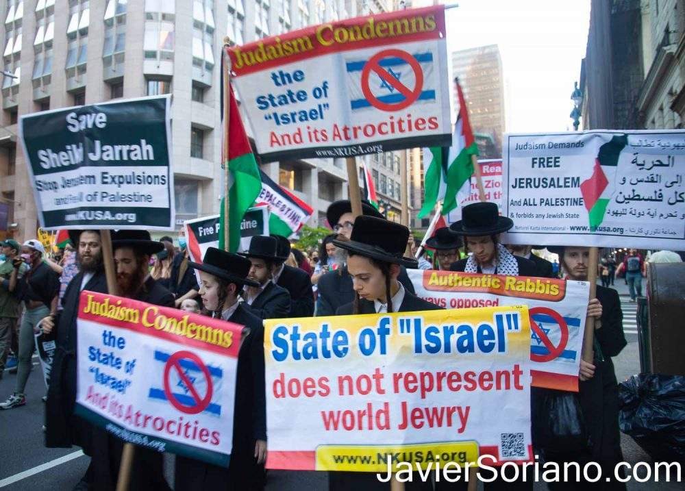 """Tuesday, June 15, 2021. Manhattan, New York City - Emergency rally to defend Palestine in front of the zionist (Israel) consulate in Manhattan, NYC. After the rally, people marched to Union Square.  THIS PHOTO: Jews of the organization Neturei Karta (www.nkusa.org) with signs that read: """"State of """"Israel"""" does not represent world Jewry"""" """"Judaism condemns the state of """"Israel"""" and its atrocities"""" """"Judaism demands FREE JERUSALEM and ALL PALESTINE and forbids any Jewish state""""   Photo by Javier Soriano/www.JavierSoriano.com"""