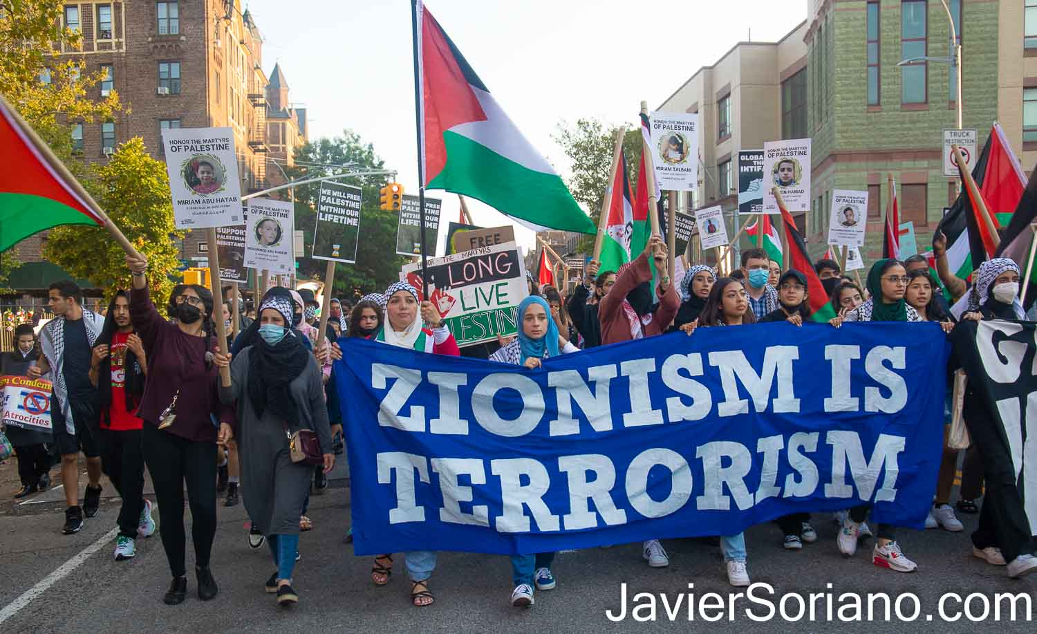 """Saturday, July 31, 2021. Brooklyn, New York City - Memorial, rally and march in Bay Ridge, Brooklyn; New York City, to honor the martyrs of Palestine. THIS PHOTO: Palestinians marching in Bay Ridge. The banner reads, """"ZIONISM IS TERRORISM."""" Photo by Javier Soriano/www.JavierSoriano.com"""