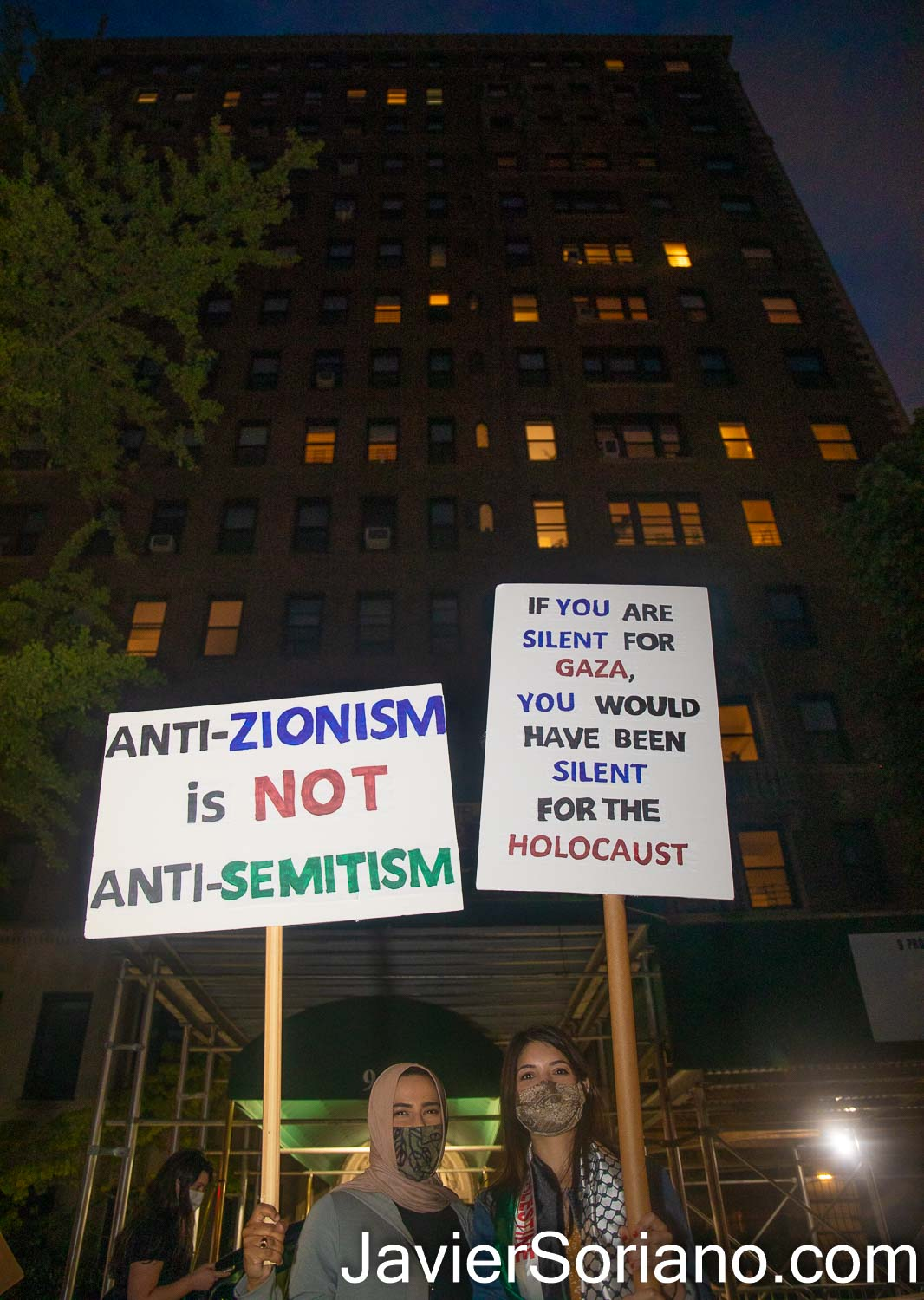 Friday, May 21, 2021. New York City – Jews, Palestinians and other New Yorkers gathered at Grand Army Plaza in the borough of Brooklyn to stand in solidarity with Palestine. After the rally, demonstrators marched to the building of the United States Senator Charles Ellis Schumer. The luxury building is in front of Prospect Park. THIS PHOTO: Two female protesters in front of Senator Chuck Schumer's building in Brooklyn, NYC. Photo by Javier Soriano/www.JavierSoriano.com